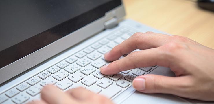 お金が借りられるところをパソコンで探す女性